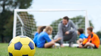 Coach,And,Team,Discussing,Soccer,Tactics,With,Ball,In,Foreground
